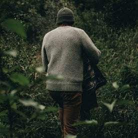 fit model wearing The Fisherman Sweater in Heather Ash, walking in brush