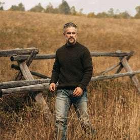 fit model wearing The Fisherman Sweater in Loden, walking in field