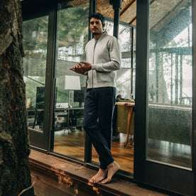 our fit model wearing The Heavy Bag Bomber in Heather Grey Fleece standing out on the porch of cabin looking at camera