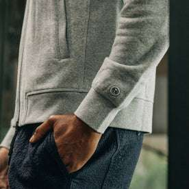 our fit model wearing The Heavy Bag Bomber in Heather Grey Fleece closeup with right hand in pocket sshowcasing embroidered TS logo on cuff