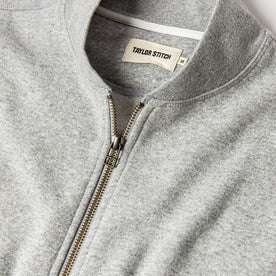 material shot of The Heavy Bag Bomber in Heather Grey Fleece top zipper, collar, and tag visible