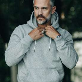 our fit model wearing The Heavy Bag Hoodie in Heather Grey Fleece pulling collar with drawstrings of hood visible