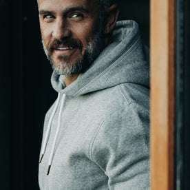 our fit model wearing The Heavy Bag Hoodie in Heather Grey Fleece closeup while looking over left shoulder smirking