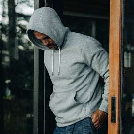 our fit model wearing The Heavy Bag Hoodie in Heather Grey Fleece with the hood up and looking down