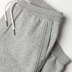 flatlay of The Heavy Bag Pant in Heather Grey Fleece with diagonal reinforced hand pocket visible