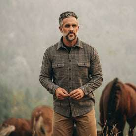 our fit model wearing The Leeward Shirt in Houndstooth in front of horses