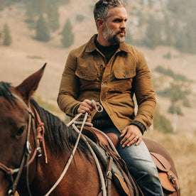 fit model wearing The Lined Long Haul Jacket in Harvest Tan Dry Wax, on horse, looking right