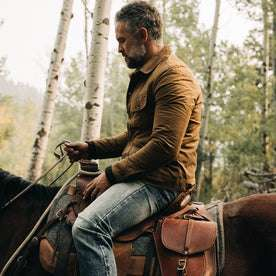 fit model wearing The Lined Long Haul Jacket in Harvest Tan Dry Wax, holding reins