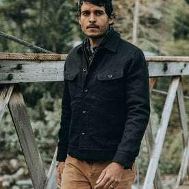 fit model wearing The Long Haul Jacket in Black Indigo Sashiko—walking on bridge