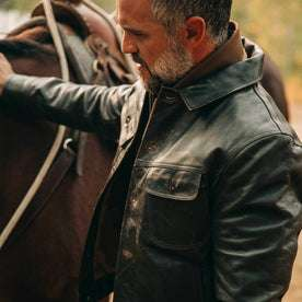 fit model wearing The Long Haul Jacket in Cola Leather, petting horse