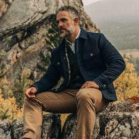 fit model wearing The Long Haul Jacket in Indigo Sashiko—sitting on rock