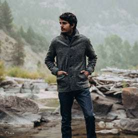 our fit model wearing The Ojai Jacket in Charcoal Wool—standing near a creek