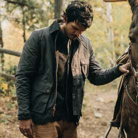 fit model wearing The Rover Jacket in Ripstop Slate Dry Wax, hand on horse