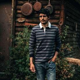 fit model wearing The Rugby Shirt in Navy Stripe, walking near cabin