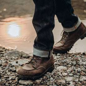 fit model wearing The Slim Jean in Cone Mills Reserve Selvage, cuffed shot over boots