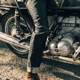 fit model wearing The Slim Jean in Black Over-dye Selvage, on bike