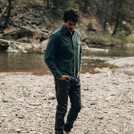 fit model wearing The Yosemite Shirt in Deep Ocean—walking near creek