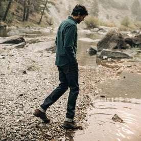 fit model wearing The Yosemite Shirt in Deep Ocean—walking into creek water