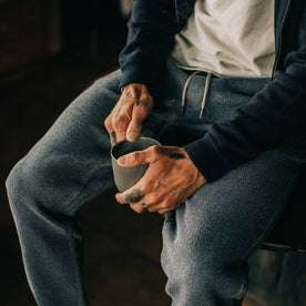 fit model wearing The Après Pant in Charcoal Waffle, sitting, holding coffee