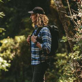 Our fit model in The Crater Shirt in Blue Plaid hiking in the forrest