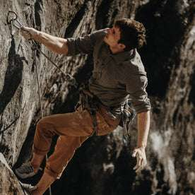 The fit model climbing in the durable Yosemite Shirt in Heather Charcoal