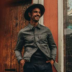 fit model wering flatlay of The Dispatch Jacket in Navy Jaspe, smiling, hands in pockets