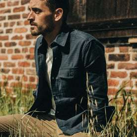 fit model wearing The Point Shirt in Navy Reverse Sateen, sitting in grass