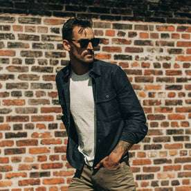 fit model wearing The Point Shirt in Navy Reverse Sateen, looking right, brick wall behind
