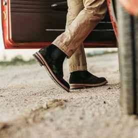 our fit model wearing The Ranch Boot in Coal Weatherproof Suede—walking toward truck