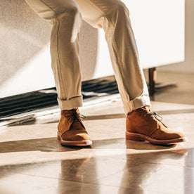 The Unlined Chukka in Butterscotch Weatherproof Suede—pants cuffed, sitting against couch
