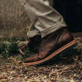 our fit model wearing The Moto Boot in Chocolate Pebble Grain—close up of left boot