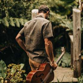 our fit model wearing The Caravan Shirt in Walnut Double Cloth—walking with guitar