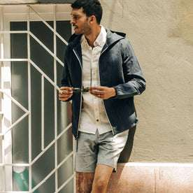 fit model wearing The Riptide Jacket in Indigo Slub, playing with sunglasses