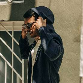 fit model wearing The Riptide Jacket in Indigo Slub, putting up hood