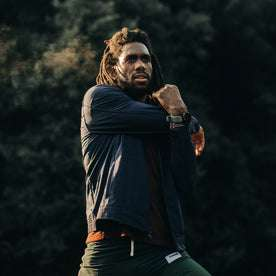 fit model wearing The Park Bomber in Navy, stretching