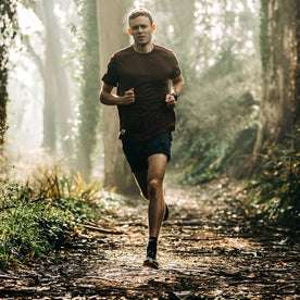 fit model wearing The Traverse Short in Navy, running on trail