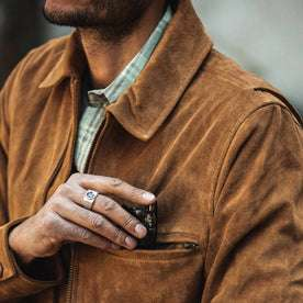 fit model wearing The Wyatt Jacket in Cognac Suede, putting sunglasses in front pocket