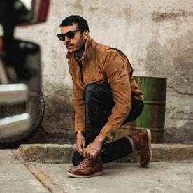 fit model wearing The Wyatt Jacket in Cognac Suede, tying his boots