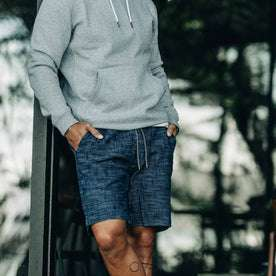 our fit model wearing The Après Short in Indigo Slub—wearing a hoodie early in the morning, cropped shot with hands in pocket