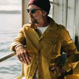 fit model wearing The Lombardi Jacket in Mustard Dry Wax, looking left