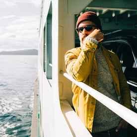 fit model wearing The Lombardi Jacket in Mustard Dry Wax, side shot on ferry