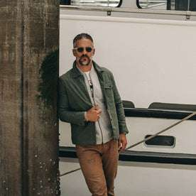 fit model wearing The Lombardi Jacket in Olive Dry Wax, standing on dock