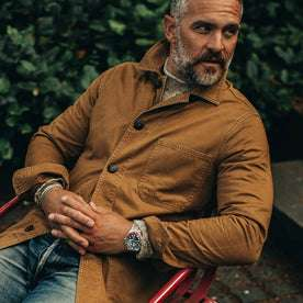 our fit model wearing The Ojai Jacket in Tobacco—sitting in a chair