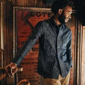 fit model wearing The BDU Shirt Jacket in Indigo Slub, smiling, hand on railing