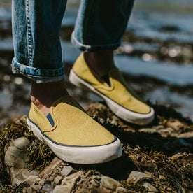 fit model wearing The Sano Slip-On in Gold Boss Duck, standing on rocks near the coast
