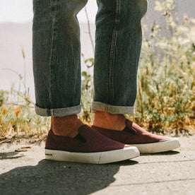 fit model wearing The Sano Slip-On in Rust Boss Duck, standing near grass