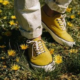 fit model wearing The Vista Sneaker in Gold Boss Duck, standing in grass