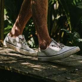 fit model wearing The Vista Sneaker in Natural Boss Duck, walking on pathway