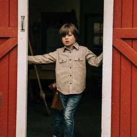 our fit model wearing The Little Yosemite Shirt in Oat Donegal—standing near a barn