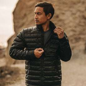 our fit model wearing The Taylor Stitch x Mission Workshop Farallon Jacket in Black—looking left on beach